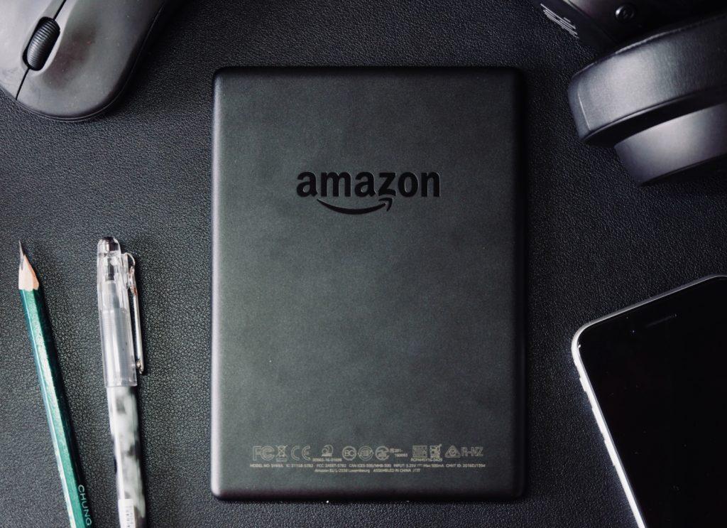 tablet preto com logotipo da amazon com caneta, lapis e telemovel ao lado